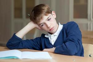 flitig förskole sitter vid skrivbordet, klassrummet foto