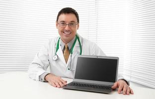 läkare sitter vid sitt skrivbord med laptop foto