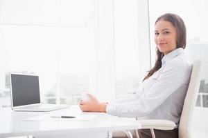 glad affärskvinna som har kaffe vid sitt skrivbord foto