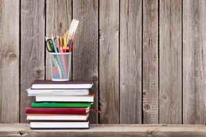 trähylla med böcker och förnödenheter foto