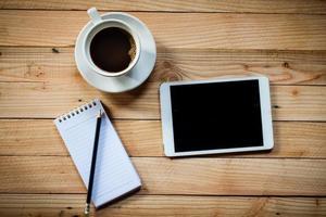 arbetsplats med surfplatta, anteckningsbok och kaffekopp