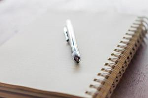 närbild spiral anteckningsbok och penna foto