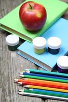 böcker, pennor och ett äpple foto