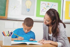 vacker lärare som hjälper eleven vid sitt skrivbord foto