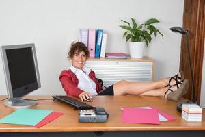kvinna kopplar av vid sitt skrivbord på kontoret foto
