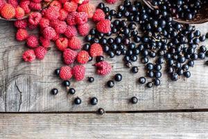 svarta vinbär och hallon på trä skrivbord foto