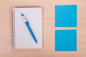 penna och papper på träbakgrund foto