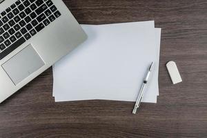 bärbar dator, papperspenna och radergummi på skrivbordet foto