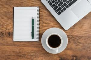 bärbar dator, anteckningsbok och kaffekopp på skrivbordet foto