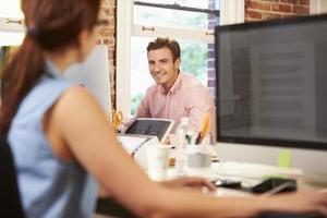 affärsman och affärskvinna som arbetar på skrivbord i office foto