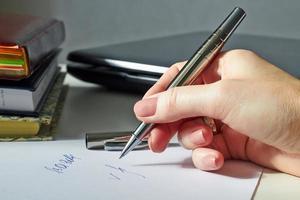affärskvinna sitter vid kontorsskrivbord undertecknar ett kontrakt foto