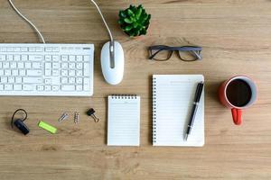 kontorstillförsel och kopp kaffe på skrivbordet foto