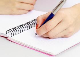 ung flicka som lär sig vid skrivbordet. över vit bakgrund foto