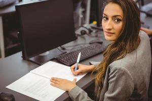leende student som sitter vid skrivbordet och skriver på anteckningar foto