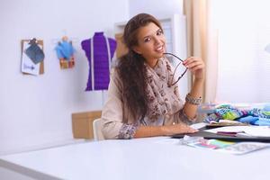 le kvinnlig modedesigner som sitter vid kontorsskrivbordet foto