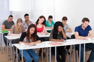 studenter som skriver vid skrivbordet foto