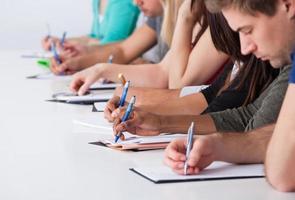 universitetsstudenter som skriver vid skrivbordet foto