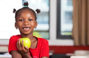 afrikansk flicka på skolskrivbordet redo att äta sitt äpple foto