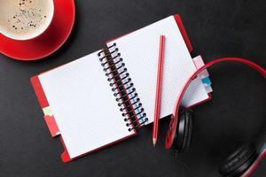 skrivbord med anteckningsblock, kaffe och hörlurar foto