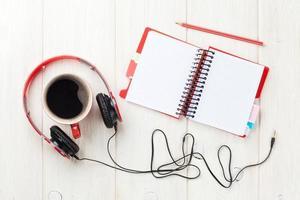 hörlurar, kaffekopp och anteckningsblock på skrivbordet foto