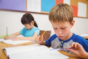söta elever som ritar vid sina skrivbord foto
