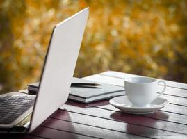 bärbar dator och kopp kaffe på skrivbordet foto