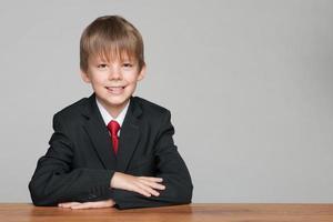 ung stilig pojke vid skrivbordet foto