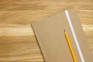 trä skrivbord topp med anteckningsbok och penna foto