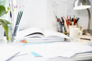 skrivbord med böcker; papper och borstar foto