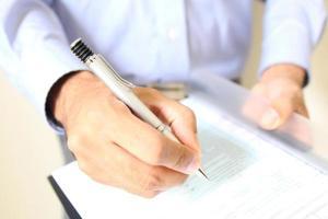 affärsman på kontorsskrivbordet undertecknar ett kontrakt foto