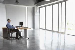 man sitter vid skrivbordet på tomt kontor foto