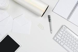 vitt skrivbord med surfplatta och tangentbord foto