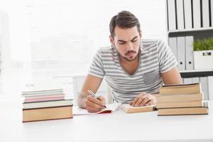 avslappnad affärsman som studerar vid sitt skrivbord foto