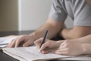 par löser sudoku i tidningen vid skrivbordet foto