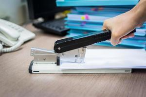 mans hand häftklammerpapper på skrivbordet foto