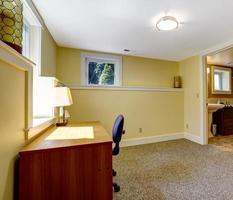 tomt kontorsrum med bokhylla och skrivbord foto