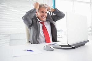 stressad affärsman vid sitt skrivbord foto