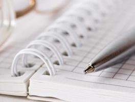 spiralkontrollerad anteckningsbok, metallpenna och glasögon foto