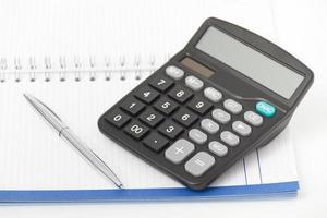 affärsidé med miniräknare, penna och anteckningsbok foto