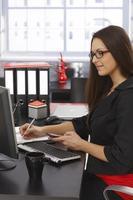 sidovy av affärskvinna vid skrivbordet foto