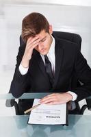 trött affärsman med faktura vid skrivbordet foto