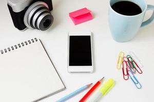 kontorsskrivbord med telefon och kamera foto