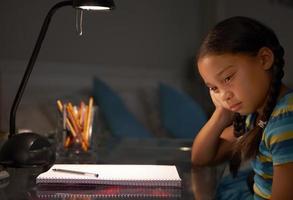olycklig ung flicka som studerar vid skrivbordet foto
