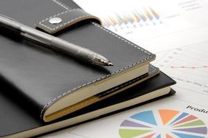 personlig arrangör och penna på affärsmaterial foto