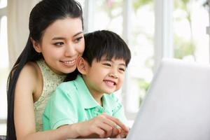 mamma och son sitter vid skrivbordet på bärbar dator