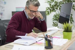man i gott humör arbetar vid skrivbordet