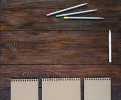 mörkbrunt träskrivbord med skissböcker och pennor foto