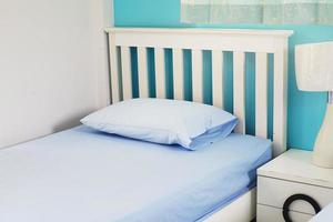 ljusblå kudde på vit säng i sovrummet foto