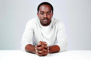 fundersam afrikansk man som sitter vid bordet foto