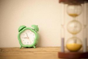 grön klocka och timglas på träbord foto